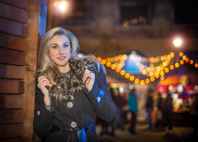 Portrait of young beautiful woman with long fair hair outdoor in cold winter evening. Beautiful blonde girl in winter clothes. With xmas lights in background royalty free stock images