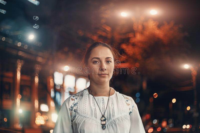 Portrait of young beautiful woman looks at camera on blurred illuminated street of night city background stock image