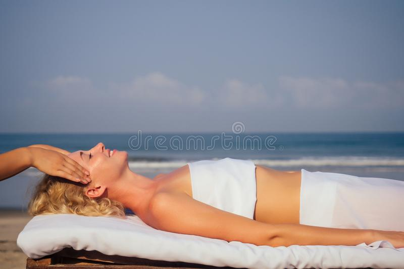Portrait of young beautiful woman on massage table beach morning getting spa on head face sholders stock photography
