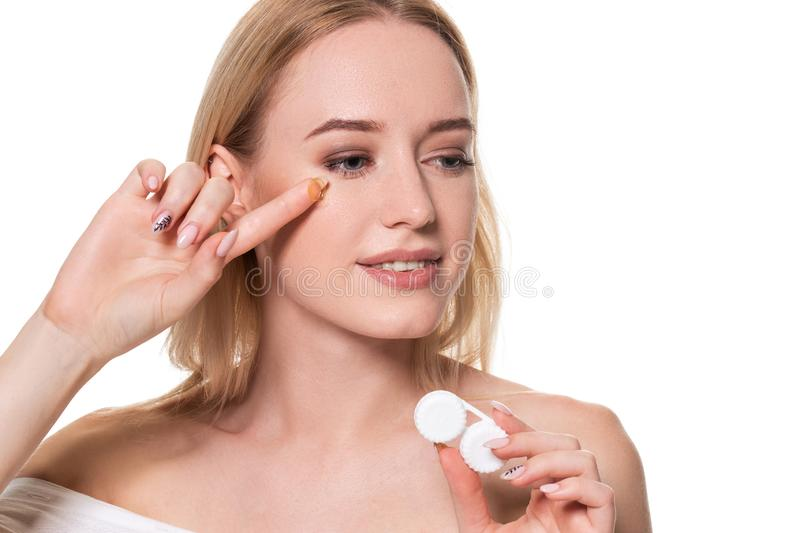 Portrait of young beautiful woman with natural makeup and contact eye lens in hand. Close-up of female model holding. White lens box. Eye care and healthy stock images
