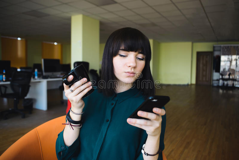 Portrait of a young, beautiful woman office worker who uses a mobile phone and holding a cup of drink. royalty free stock photo