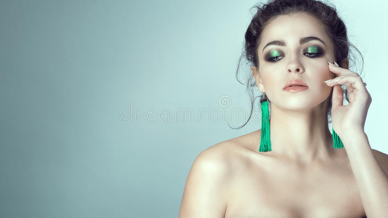 Portrait of young beautiful woman with perfect skin and bright make-up touching her face with manicured fingers. Long green fabric earrings in her ears. Her royalty free stock photo