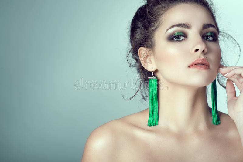 Portrait of young beautiful woman with perfect skin and bright make-up touching her face with manicured fingers. Long green fabric earrings in her ears. Her stock image