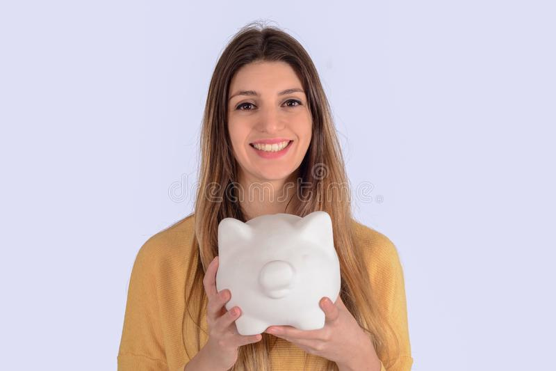 Young woman with piggy bank. Portrait of young beautiful woman with piggy bank on studio. Save money concept stock photos