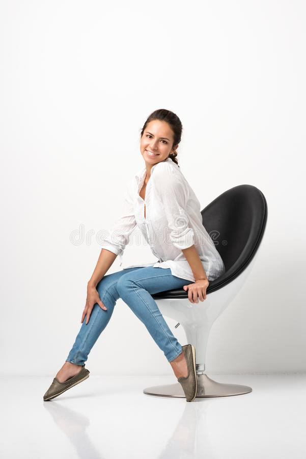 Portrait of young beautiful woman posing in a chair. White shirt and jeans royalty free stock photos