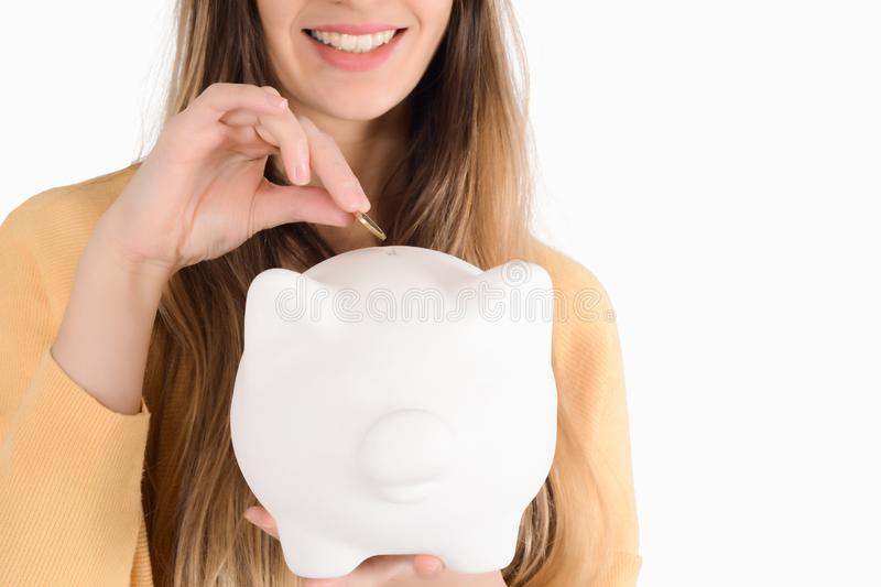 Young woman with piggy bank. Portrait of young beautiful woman putting a coin in a piggy bank on studio. Save money concept stock photos