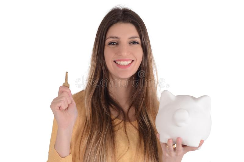 Young woman with piggy bank. Portrait of young beautiful woman putting a coin in a piggy bank on studio. Save money concept stock photo