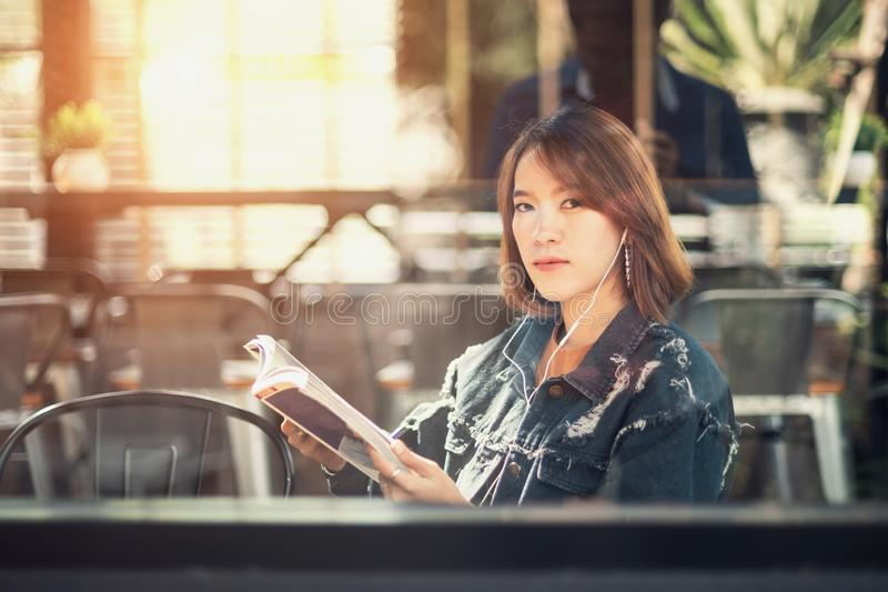 Young woman reads and listens to music stock photo