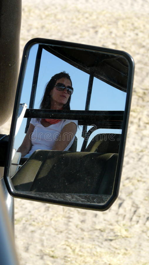 Portrait of young beautiful woman reflected on the car`s mirror of a safari jeep during a morning game in Okavango Delta, Botswana royalty free stock image