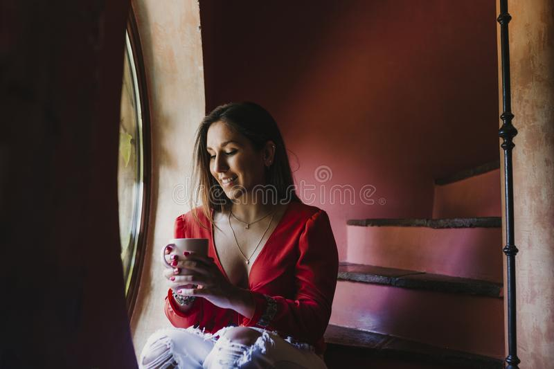 Portrait of young beautiful woman sitting by the window relaxed at home holding a cup of tea of coffee. Lifestyle indoors stock photography