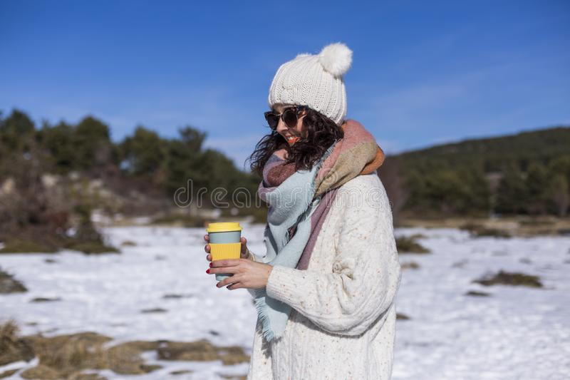 Portrait of a young beautiful woman in the snow holding a cup of coffee or tea. Sunny weather. Wearing warm clothes. Lifestyle stock image