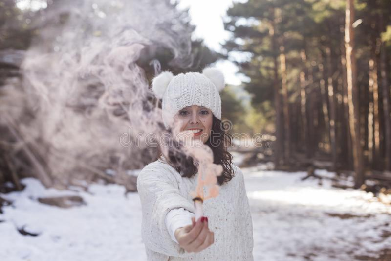 Portrait of a young beautiful woman in the snow holding a yellow bomb smoke. Sunny weather. Wearing warm clothes. Winter lifestyle stock photos