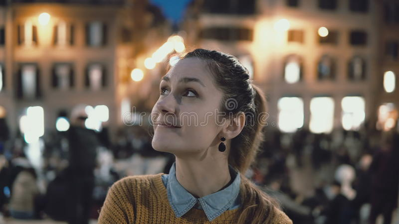 Portrait of young beautiful woman standing in the city centre in evening. Student girl looks at camera, smiling. royalty free stock image
