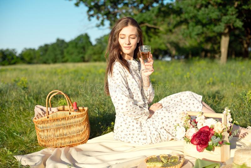 Portrait of a young beautiful woman standing with food basket in the garden with decorated dinner place during the sunny royalty free stock images
