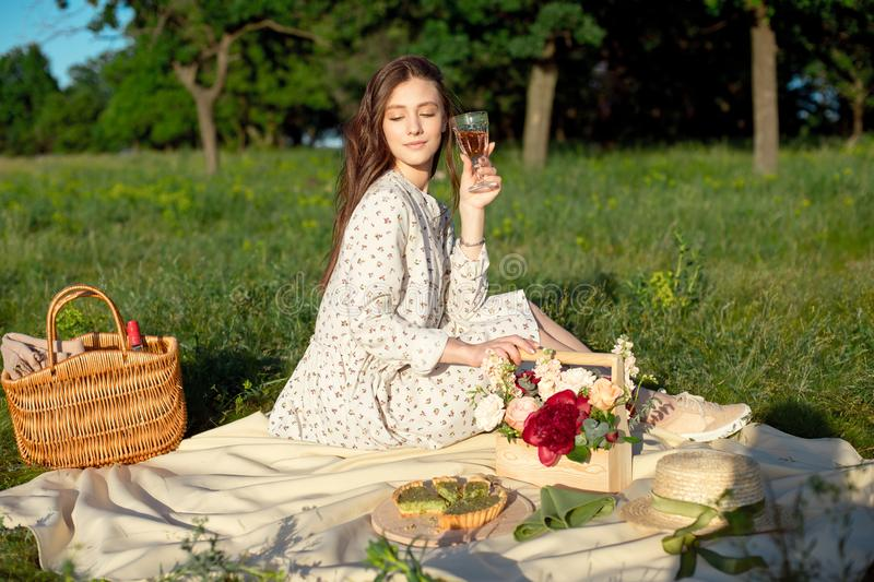 Portrait of a young beautiful woman standing with food basket in the garden with decorated dinner place during the sunny stock image