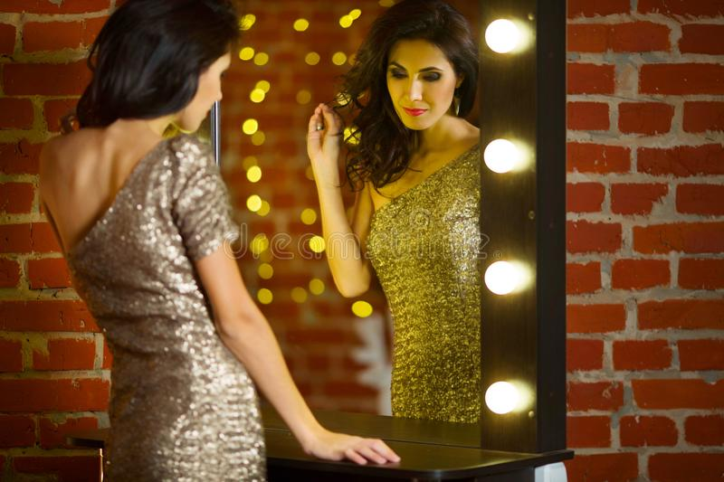Portrait of young beautiful woman standing near mirror with stock image