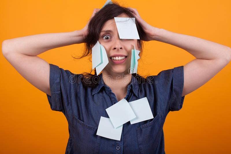 Portrait of young beautiful woman stressed with sticky notes on clothes and body standing over yellow background in royalty free stock photography