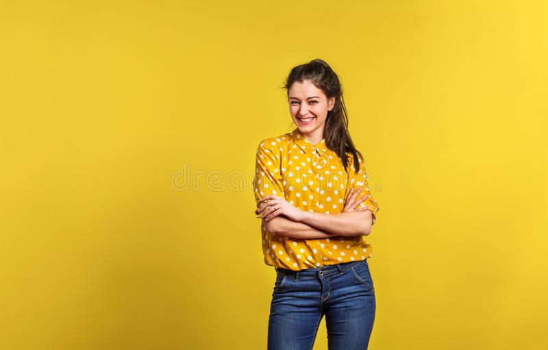Portrait of a young beautiful woman in studio on yellow background. stock image