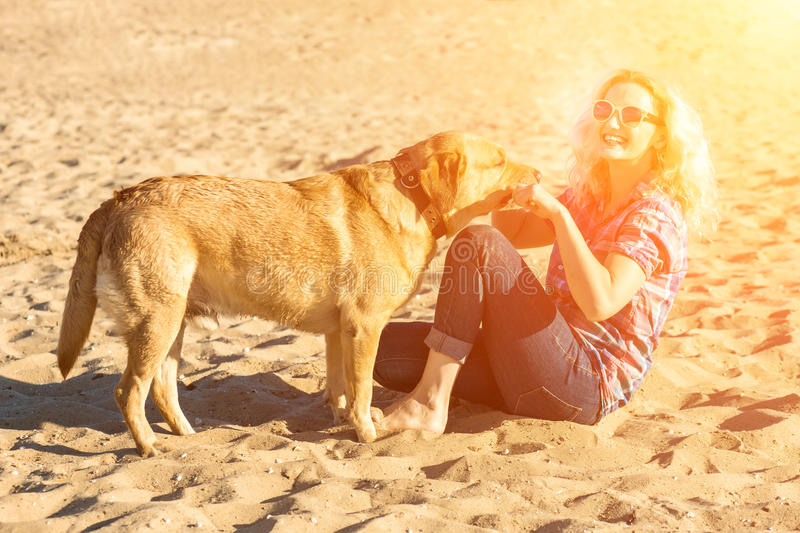 Portrait of young beautiful woman in sunglasses sitting on sand beach hugging golden retriever dog. Girl with dog by sea stock photos