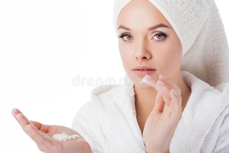 Portrait of a young beautiful woman in a Terry robe and with a towel on her head. Beauty and skin care stock image