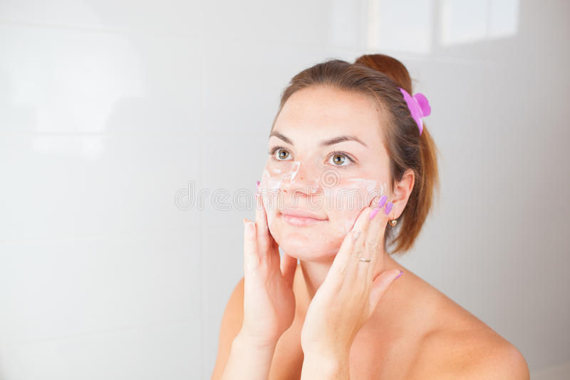 Portrait of young beautiful woman using cosmetics cream stock photos