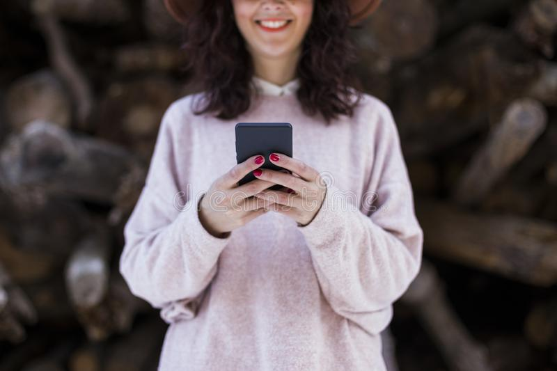 Portrait of a young beautiful woman using mobile phone outdoors and smiling. Blurred wood trunks background. Technology and royalty free stock images
