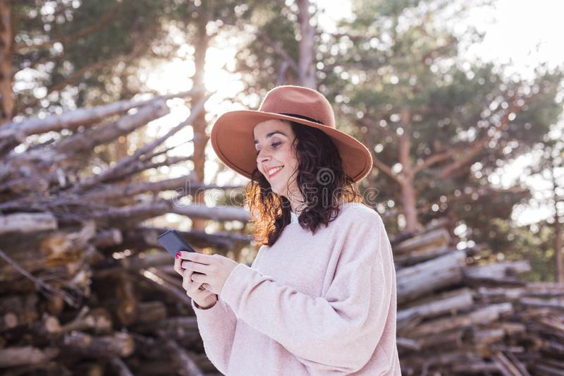 portrait of a young beautiful woman using mobile phone outdoors and smiling. Blurred wood trunks background. Technology and stock image