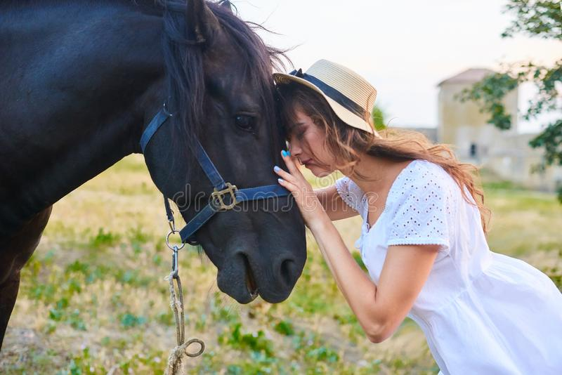 A girl dressed in a white peasant dress walks through the territory of an ancient castle and girl strokes a horse royalty free stock image