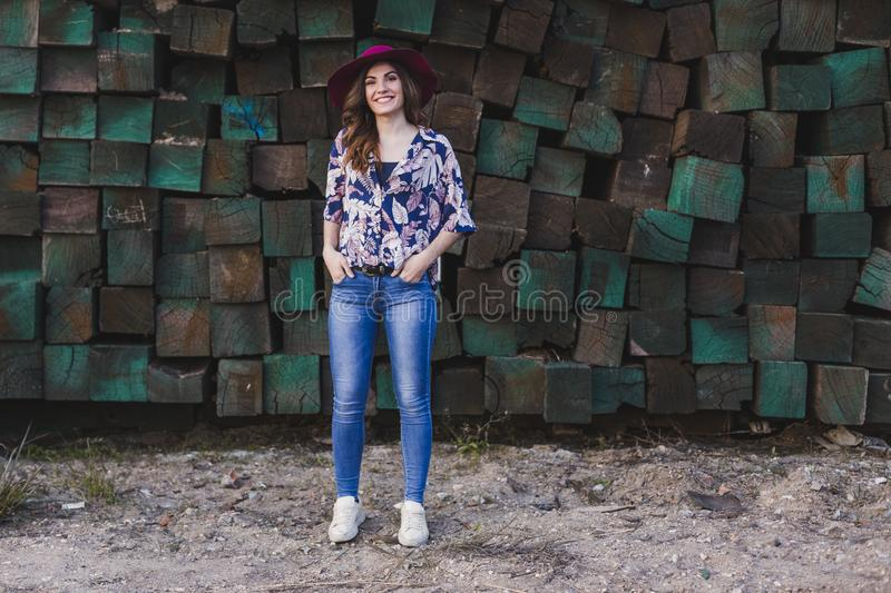 portrait of a young beautiful woman wearing casual clothes and a modern hat, standing over green wood blocks background and stock photos
