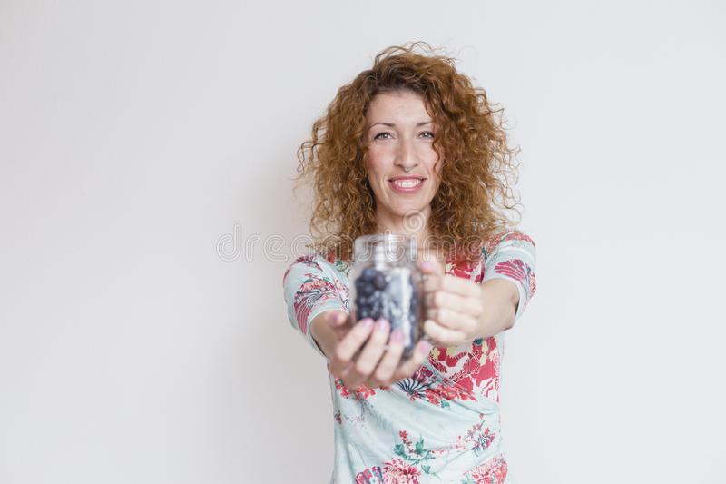 Portrait of a young beautiful woman wearing a colorful flowers dress over white background. She is smiling and holding a jug of stock images