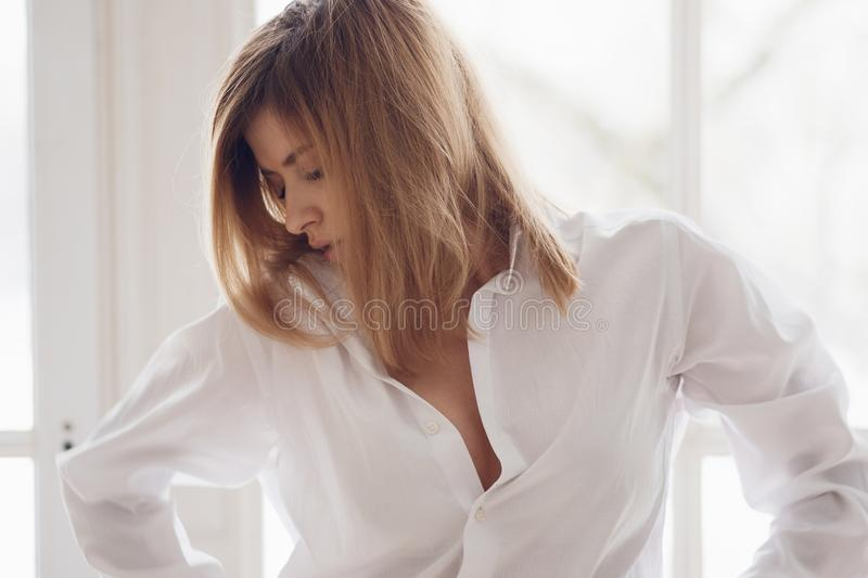 Portrait of a young beautiful woman at the window. Girl in white shirt royalty free stock images