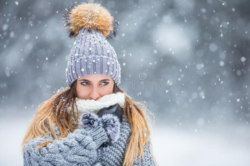 Portrait of young beautiful woman in winter clothes and strong snowing.  royalty free stock photo