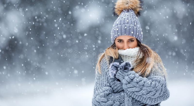 Portrait of young beautiful woman in winter clothes and strong snowing.  royalty free stock photography