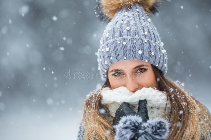Portrait of young beautiful woman in winter clothes and strong snowing.  stock photo