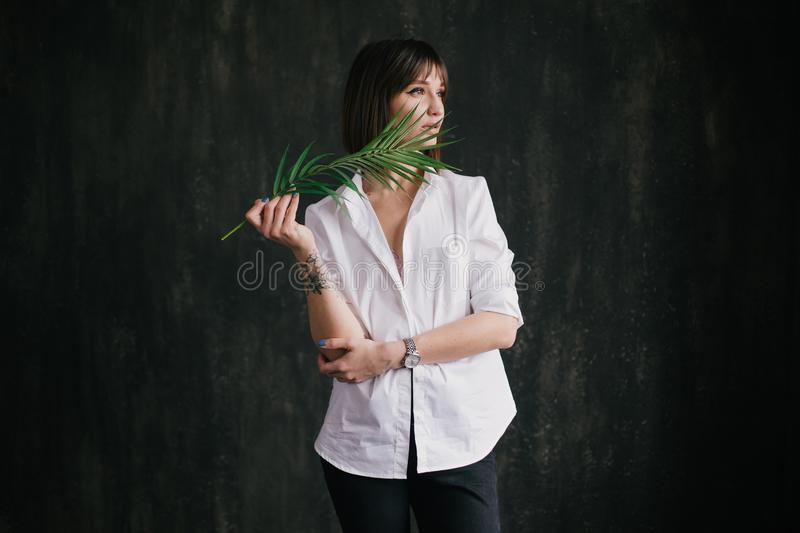 Portrait of a young beautiful woman witn a fern leaf stock photo