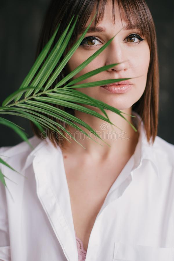 Portrait of a young beautiful woman witn a fern leaf stock images