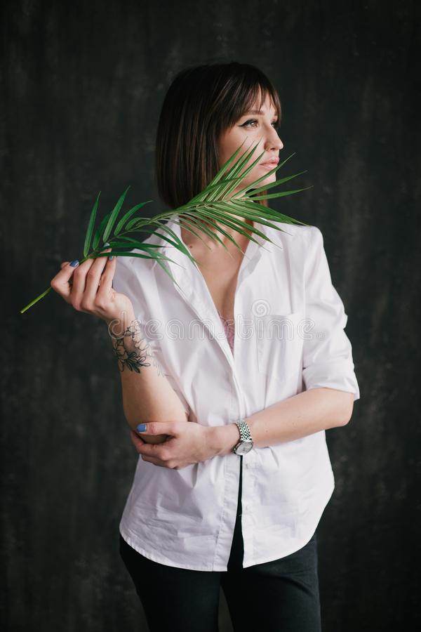 Portrait of a young beautiful woman witn a fern leaf royalty free stock image