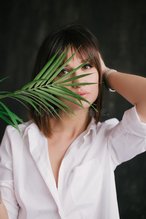 Portrait of a young beautiful woman witn a fern leaf royalty free stock photos