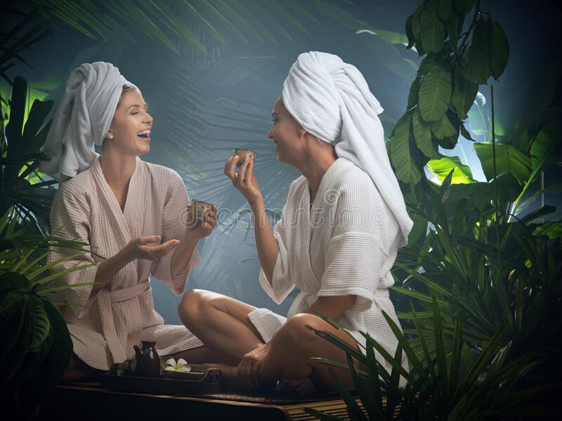 Beautiful women drinking tea  in spa environment. Portrait of young beautiful women drinking tea  in spa environment stock photography