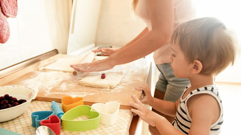 Portrait of young beautiful woman teaching her little child boy making cookies and baking pies on kitchen at home royalty free stock photo