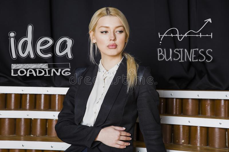 Portrait of a beauty blond busiensswoman in a black suit standing near white sketchs. Portrait of a young beauty blond busiensswoman in a black suit standing royalty free stock photo