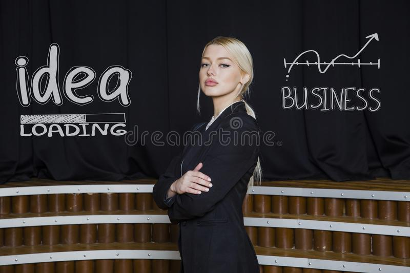 Portrait of a beauty blond busiensswoman in a black suit standing near white sketchs. Portrait of a young beauty blond busiensswoman in a black suit standing royalty free stock photography