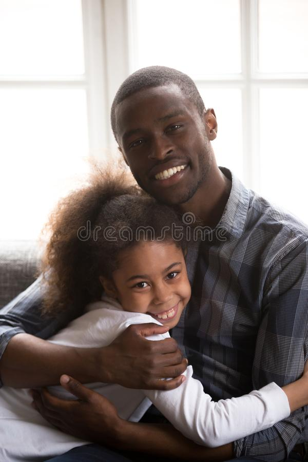 Portrait of young black dad hugging with teen daughter stock photos