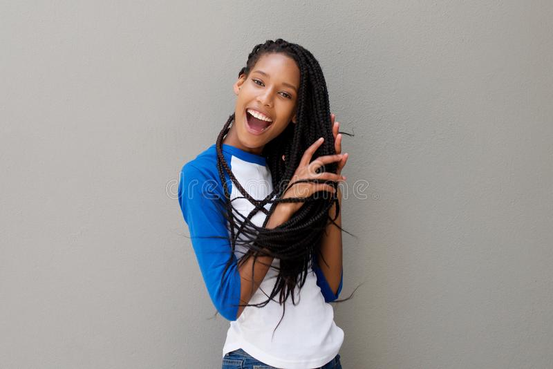 Young black woman with braided hair laughing against gray wall stock images