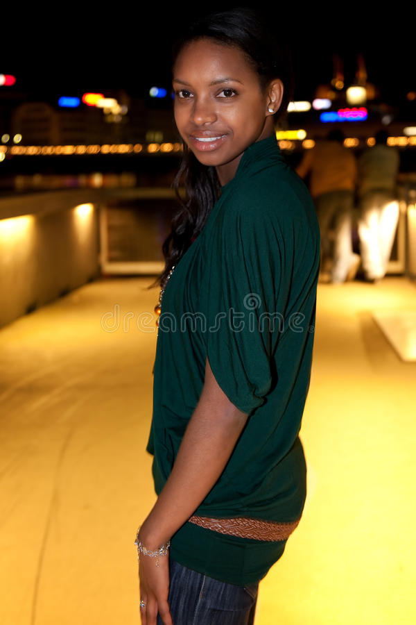 Portrait of young black woman in city at night. stock photo