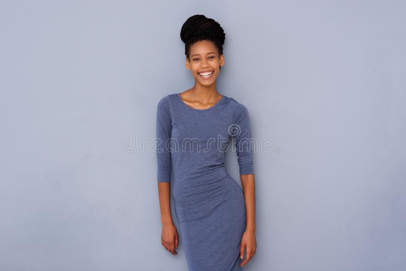 Young black woman smiling against gray wall royalty free stock image