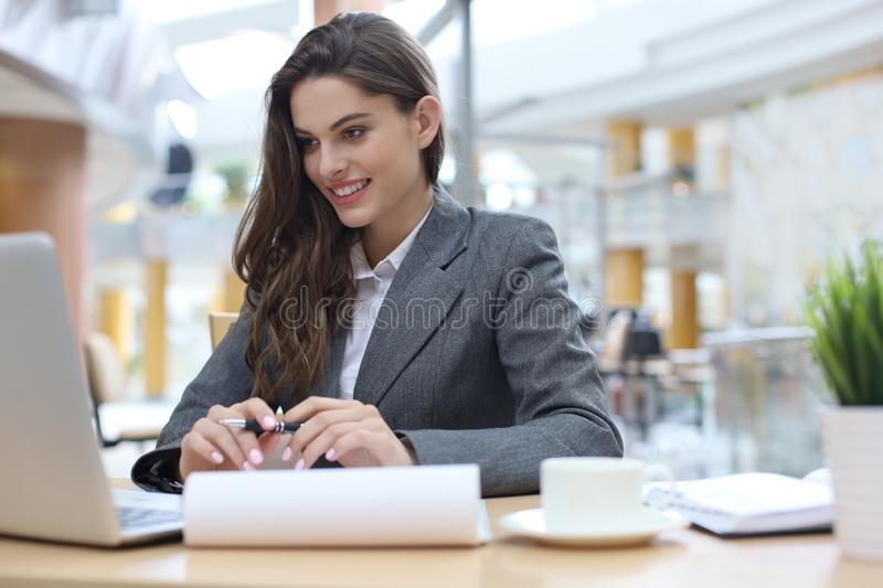 Portrait of a young blond business woman using laptop at office royalty free stock photography