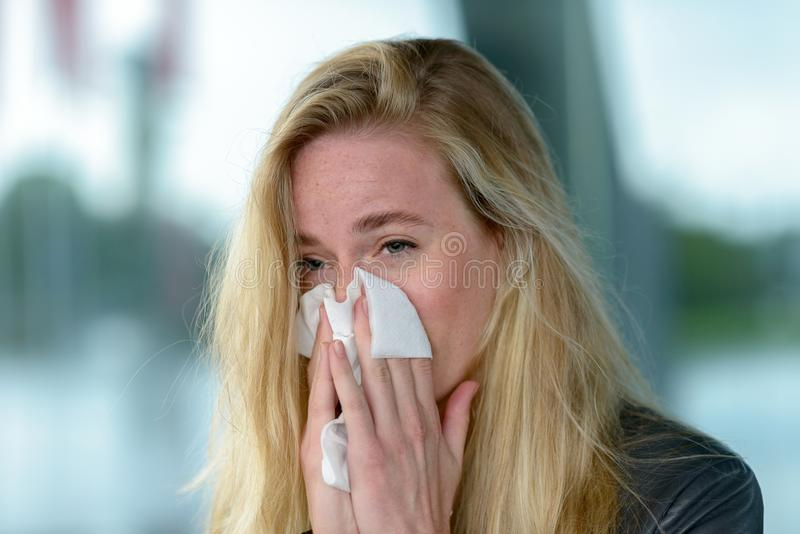 Young blond woman with hay fever. Portrait of young blond woman blowing her nose into tissue, while having her eyes opened stock images