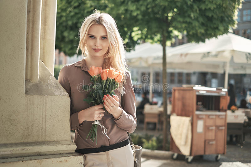 Portrait of a young blond woman with a bunch of roses royalty free stock images