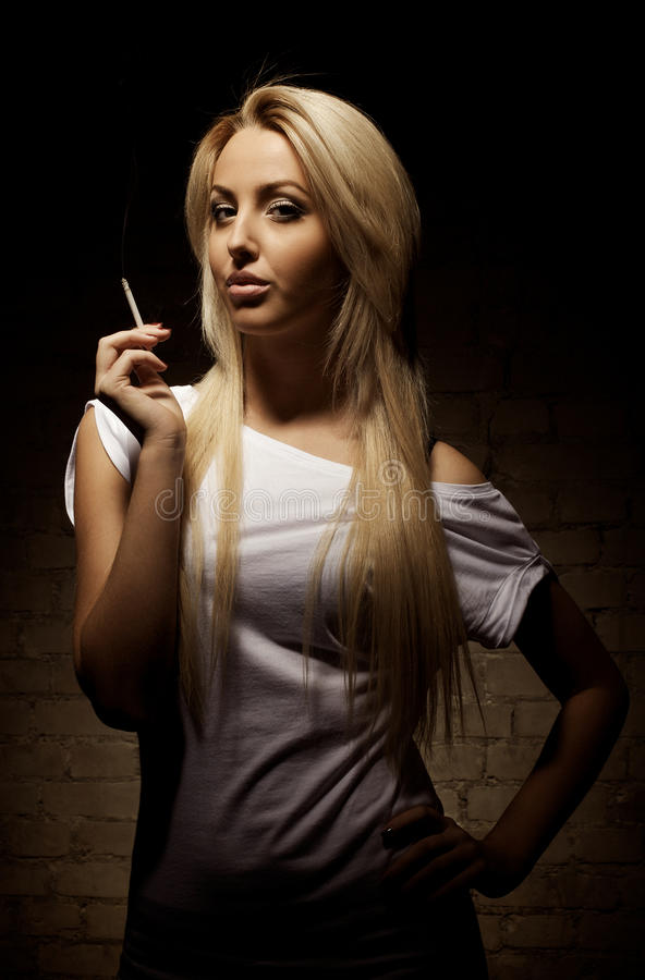 Portrait of young blond woman with a cigarette. On dark background. Sepia toned stock photos